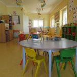 Sala para crianças, com uma mesa, quarto cadeiras e vários jogos e materiais de ensino